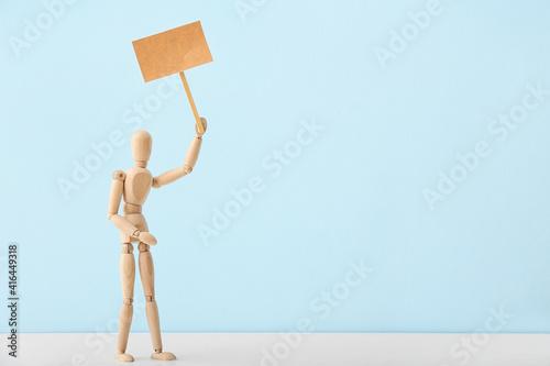 Obraz na plátně Wooden mannequin with blank placard on color background