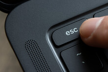 Finger Pressing The Escape Key On A Black Laptop Computer.