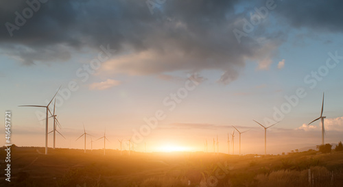 Fototapeta Silhouette of wind turbines. Beautiful view of wind generators in the mountain hill at sunset. obraz