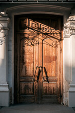Antique Architecture, Old Vintage Closed Wooden Door With Massive Handles Entrance To The Staircase With An Arch With Beautiful Shadows From The Forged Twisted Decorative Visor