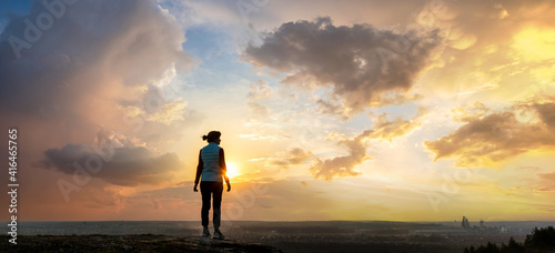 Obraz Silhouette of a woman hiker standing alone enjoying sunset outdoors. Female tourist on rural field in evening nature. Tourism, traveling and healthy lifestyle concept. - fototapety do salonu