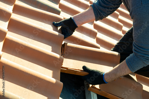 Fototapeta Closeup of worker hands installing yellow ceramic roofing tiles mounted on wooden boards covering residential building roof under construction. obraz