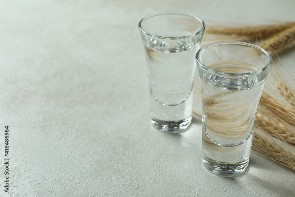 Fototapeta Shots of vodka and spikelets on white textured table