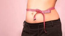 Bow Of Centimeter Ribbon On The Waist Of A Woman, The Concept Of Weight Loss, Healthy Lifestyle.