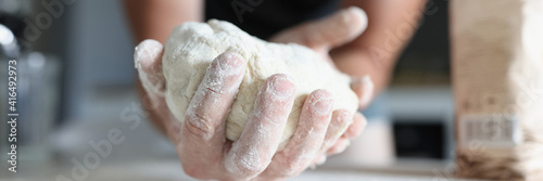 Canvas Print Man's hand holds the dough over table where flour is scattered