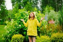 Happy Kid Girl In Yellow Raincoat Playing And Having Fun In Summer Garden Under The Rain