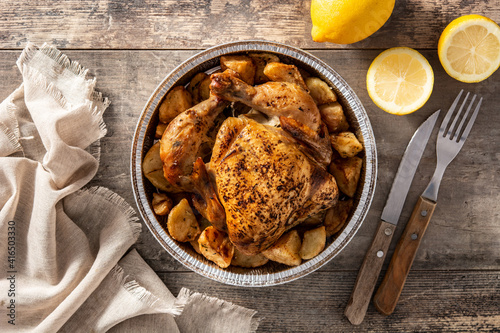 Fototapeta Delivery roasted chicken with potatoes on wooden table. Top view obraz