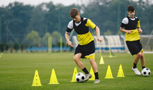 Boys On Soccer Football Training. Young Players Dribble Ball Between Training Cones. Players On Football Practice Session. Soccer Summer Training Camp