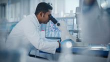 Medical Research Laboratory: Male Scientist Looking Under Micrsocope, Analyzing Samples. Advanced Scientific Lab Biotechnology, Medicine, Microbiology, Drugs Development.
