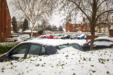 Cars Parked On British Street Under Winter Snow Fall In England Uk