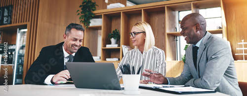 Three diverse businesspeople laughing while working together in an office