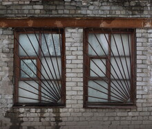 Two Windows Covered With Rusty Metal Bars In An Old White Brick Wall