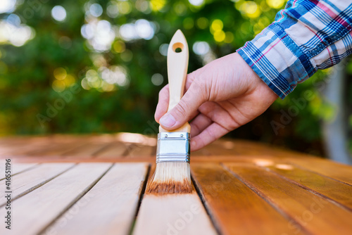 a hand holding a brush applying varnish paint on a wooden garden table - painting and caring for wood with oil