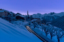 Snow Covered Village Of Guarda Lit By Car Trail Lights During A Blue Winter Dusk, Lower Engadine, Graubunden Canton, Switzerland,  Europe