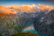 Man Standing On Rocks Looking At Clouds At Sunset Over Lake Limmernsee, Aerial View, Canton Of Glarus, Switzerland, Europe