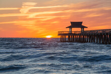 View Across The Gulf Of Mexico From Beach Beside Naples Pier, Sunset, Golden Sky Above Horizon, Naples, Florida, United States Of America, North America