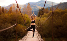 Yoga Outdoor. Young Woman Do Yoga Balance Exercises. Yoga Meditation On Bridge Over River With Mountains Background. Concept Of Healthy Lifestyle And Relaxation.