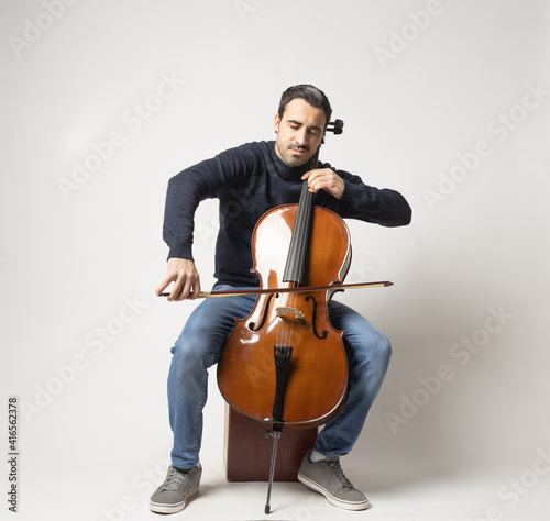 Fotografering young man playing cello on the white background