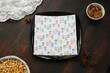 Serwetka we wzorki na czarnym talerzu kwadratowym na brązowym stole drewnianym