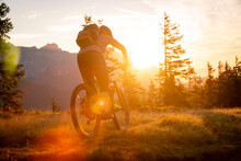 A Mountain Biker Is Doing Off-road Moutain Biking Early Morning At Sunrise.