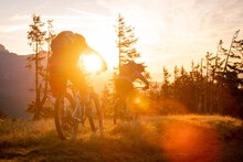 Two Mountain Bikers Are Doing Off-road Moutain Biking Early Morning At Sunrise.