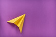 Yellow toy paper plane on a colored background.