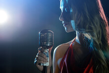 Silhouette Of The Singer With A Microphone On Dark Background With Blue Light