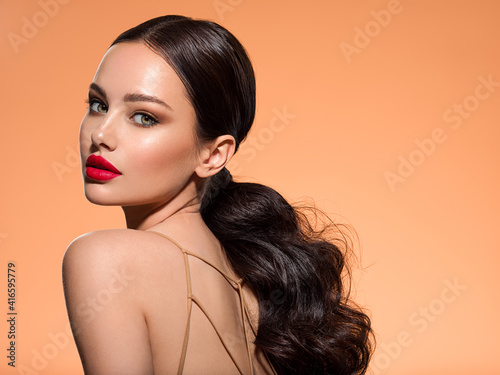 Obraz Beautiful white girl with a red lipstick on lips. Stunning brunette girl with long hair tail.  Closeup face of young beautiful woman with a healthy clean skin. Pretty woman with bright makeup - fototapety do salonu