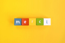 Merci - Word Made From Colored Wooden Blocks. Painted Cubes With Letters On Yellow Background. Conceptual Photo. Top View. Selective Focus. Copy Space.