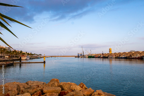 Port and boathouse on Gandia beach, with views of the sheds, the lighthouse and the fish market, with some cranes and plowed boats, and a cloudy sky at sunset, on a winter afternoon Fototapete