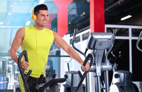 Fototapeta Man using modern elliptical machine in gym, space for text obraz