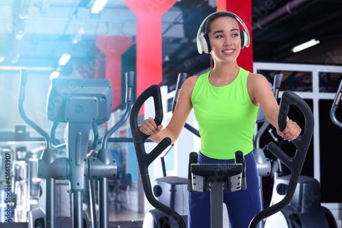 Fototapeta Woman with headphones using modern elliptical machine in gym obraz