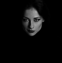 Angry Strong Look Woman With Smirking Smiling Posing Isolated On Dark Shadow Black Background. Closeup Portrait In Deep Low Key Light Shadows. Art.