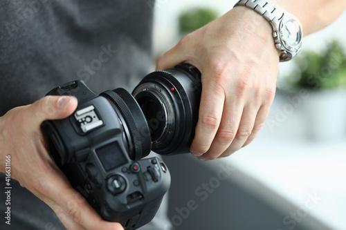 Canvas Male hands putting on modern digital camera professional lens