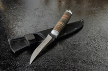 Elegant Hunting Knife In A Sheath With A Leather Handle On A Black Textured Background