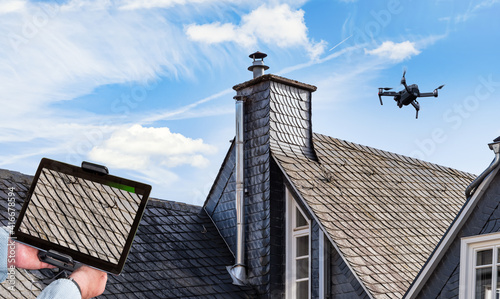 Fotografie, Obraz Drone in the air inspecting the roof of the house