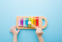 Baby Hand Holding Hammer And Playing Colorful Xylophone On Light Blue Table Background. Closeup. Music Toy Instrument Of Development For Little Kids. Point Of View Shot. Top Down View.