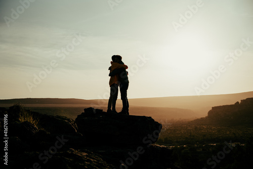 Fototapeta Silhouette caucasian husband and wive hugging on top of mountain at sunset while