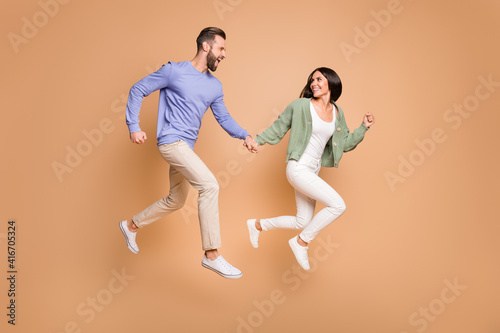 Obraz Full length body size view of nice cheerful life partners jumping holding hands running leisure isolated on beige pastel color background - fototapety do salonu