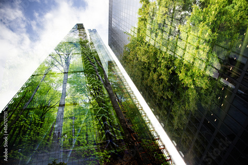 green city - double exposure of lush green forest and modern skyscrapers windows - fototapety na wymiar