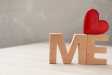 Phrase Love Me Made Of Red Heart And Wooden Letters On White Table, Closeup. Space For Text