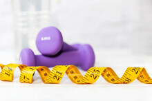 Close Up Measuring Tape.  Diet Health Planning And Workout For New Life. Sport Exercise Equipment Workout Gym. Dumbbells Background