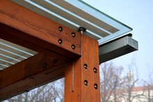 Wooden Structure Of The Bus Stop, The Shelter Of The Gazebo Pergola. The Roof And Walls Are Lined With Glass. The Glass Is Anchored With Stainless Steel Couplings. Ceiling Glass Is White Striped, Sun