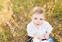 A Blue-eyed Little Boy In A White Shirt Is Sitting In The Grass