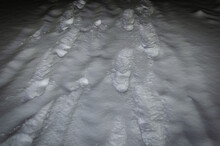 Footprints On A Snowy Road At Night.
