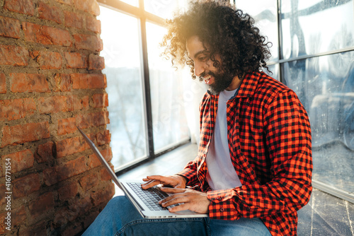Canvas Print A dark-skinned Arab with an Afro hairstyle is working at a laptop in the sunlight