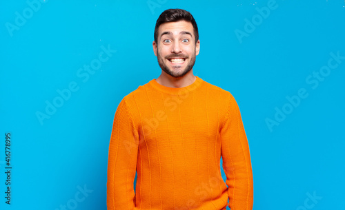 фотография handsome adult blond man looking happy and goofy with a broad, fun, loony smile