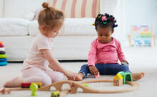 Cute Toddler Baby Girls Playing Toys Together On The Carpet