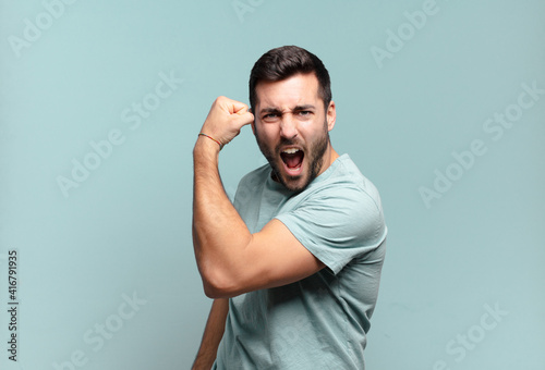 Leinwand Poster young handsome adult man feeling happy, satisfied and powerful, flexing fit and