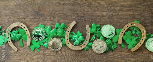 St Patricks Day border of shamrocks, gold coins on rustic wooden background